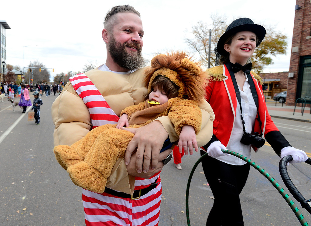 . Conrad Skelton carries his son Oakley and he and his wife April march during the Halloween Parade in Longmont on Saturday. For more photos and video go to timescall.com Paul Aiken Staff Photographer Oct 28 2017