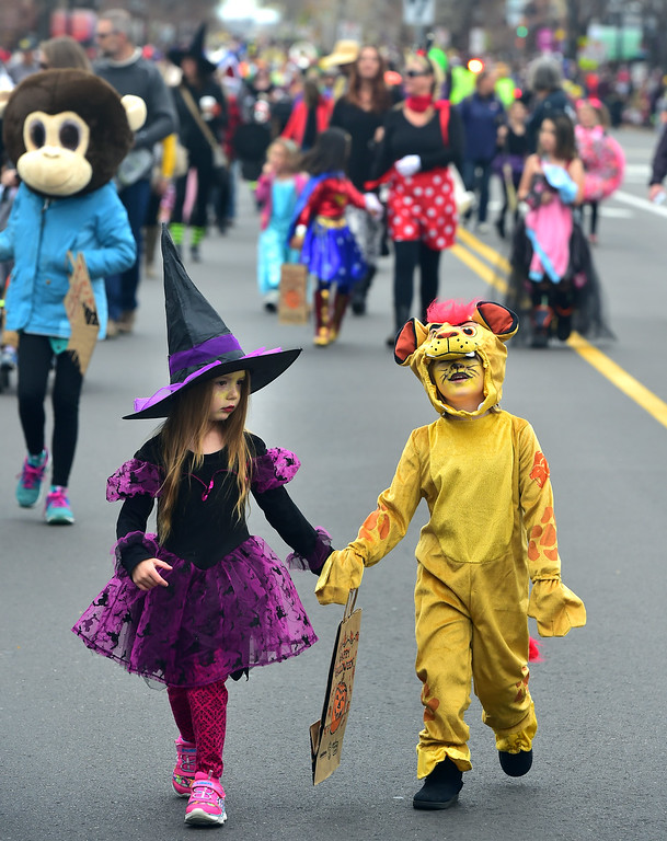 . Abbagail Farias, 4, and Gueneveve Williamson march down Main Street during the Halloween Parade in Longmont on Saturday. For more photos and video go to timescall.com Paul Aiken Staff Photographer Oct 28 2017