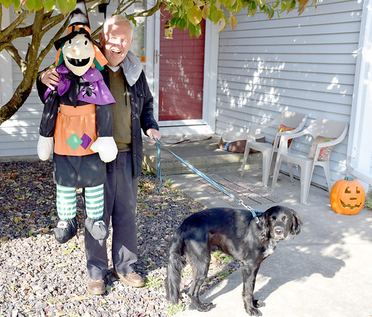 Joe Reynolds hugs a witch dangling from his tree on North Pelican Street in Effingham. Pictured with Reyonlds is Curly his black Halloween dog. Charles Mills photo