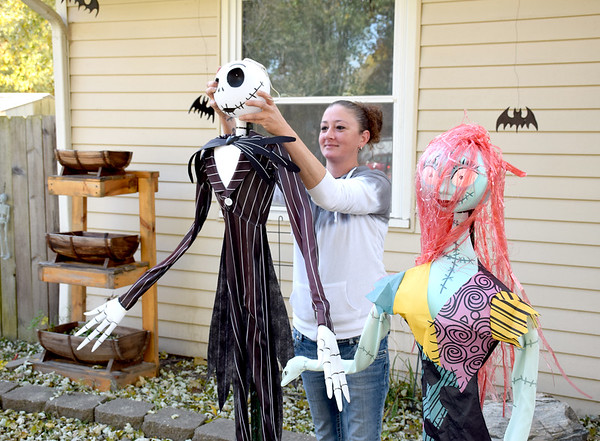 "Chris Houghton of Watson adjusts the head of ""Jack"" one of several Halloween decorations in her yard. Charles Mills photo"