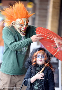 5-year-old Lillyann Stewart hangs out with her scary clown costumed Dad Jacob Stewart in front of his business Gypsy Rose during the Treat Street program in downtown Chico, Calif. Friday Oct. 31, 2014. (Bill Husa -- Enterprise-Record)