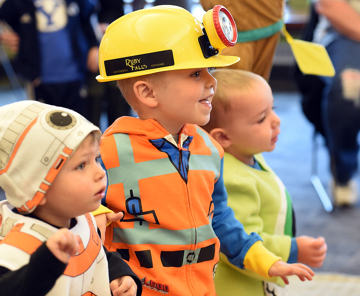 Harrison Thompson, 2, left, Charlie Thompson, 4, center, and Owen Steele, 1, right, dance to a song in their costumes Tuesday, Oct. 31, 2017, during story time at the Loveland Public Library.  (Photo by Jenny Sparks/Loveland Reporter-Herald)