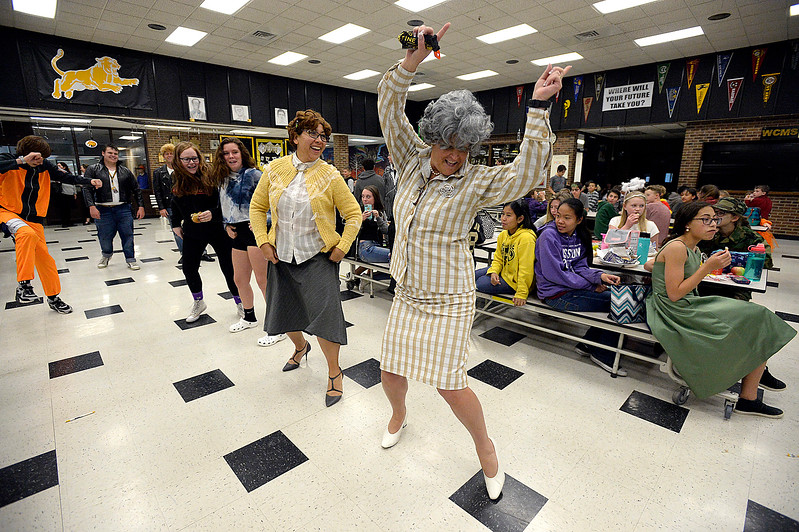 "Walt Clark Middle School principal Christine Smith, right, dressed as Principal McGee from ""Grease"", and assistant principal Christine Manzanares, left, dance to Greased Lightning Tuesday, Oct. 31, 2017, for students during lunch at the school in Loveland. Staff at the school dressed as characters from the movie and did a flash mob style dance during lunch for Halloween.    (Photo by Jenny Sparks/Loveland Reporter-Herald)"