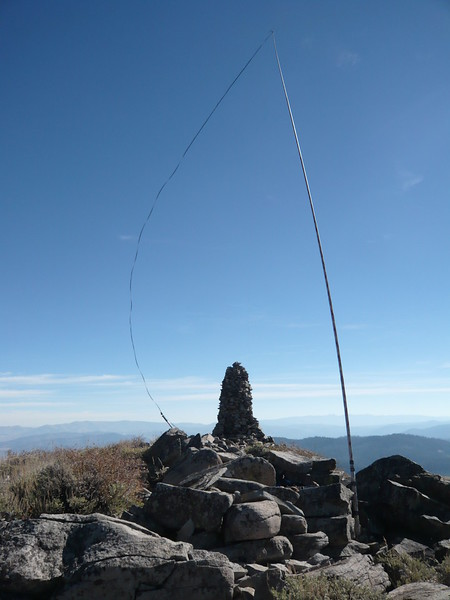The summit ridge is narrow, rather short and without any trees. I ended up placing my 28' Jackite pole midway along the ridge so that I would have room to secure the ends of my 88' doublet antenna. It was breezy, 15-20 mph gusting to 25 mph. My twinlead feedline is being bowed eastward from the prevailing west wind. The ridge was steeply sloped on each side and my antenna wire was running northwest-southeast.