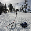 My AlexLoop with the top of the Lakeview chair lift to the right and one of the ski area boundary markers to the left. My KX3 is set up on my ski pack and I just sat on my gloves next to the pack to operate. The little elevated structure directly behind the center of my ALexLoop is a heated ski patrol shack.