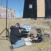 Dave decided that his lawn chair would be best used as a radio desk. He is making some final adjustments to his Yaesu FT-897 radio and confirming that his Outbacker antenna's SWR is within limits. He's sitting at the base of my Buddipole mast that is supporting my dipole (wire) antenna. Note the sign in the background, more on that later.
