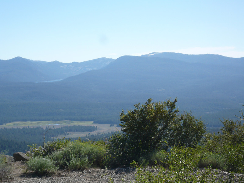 """Looking to the southwest with the Sierra crest forming the skyline. Kyburz Flat is the grassy area and Highway 89 runs north to south just past the far edge of the flat. The lake visible up in the mountains is Independence Lake and Mt. Lola (W6/NS-111) is the large mountain to the right of it with its southern slope appearing to """"touch"""" the lake."""