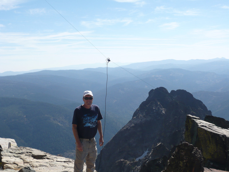 My antenna and I. As you can see, it wasn't very high above the summit itself. However, there is a 400-500' high sheer cliff about 5 feet behind me... so the antenna was electrically very-very high.
