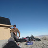 I've just arrived at the top. I took off my jacket and vest, dumped my backpack's contents on the ground and am ready to setup the antenna and radio. The building behind me will hopefully block a lot of the wind that is expected to come from the west. At this point, it is dead calm and actually kind of warm. This is a good thing, because I really look goofy wearing my fur-lined Elmer Fudd hat in the foreground.