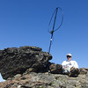 Sitting at my operating spot on the summit ridge with my Alexloop erected on a Buddipole shockcord mast. The mast base is crammed between the two rocks, and I added a few more small rocks to prevent it from turning. The smaller rock between the Alexloop and I made for a nice operating bench.
