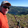 "On the summit at the summit marker (a pile of rocks with an old fir branch sticking up out of it). The shot is looking north with Bowman Lake below and Sierra Buttes W6/NS-139 on the skyline behind it (the bill on my cap is blocking half of it). Sierra Buttes is still my favorite SOTA summit, <a href=""http://www.grizzlyguy.com/HamRadio/SOTA-Activation-9202012-Sierra"">I activated it back in 2012</a>. Pinoli Ridge W6/NS-216 is the big ridge this side of Sierra Buttes that touches the skyline on either side of Sierra Buttes. <a href=""http://www.grizzlyguy.com/HamRadio/NA-SOTA-Day-Overnight-4-summit"">I camped on that one a few years ago for NASOTA day</a>."