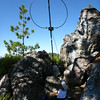 My perch, it even had some shade. I had a great shot to the south, a decent one to the west, but my shot east was basically paralleling a long wall of granite boulders (see next photo). I called CQ on 20m, quickly got two calls from stations down south, but an additional 10 minutes of CQ-ing turned up nothing. I tried 30m, but had no callers at all. I thought that minerals in the rocks might be compromising my signal to the east, so I packed up and climbed up a steep boulder gulley to try and find a better operating spot up above. <br /> <br /> I later learned that the SOTA spotting system was malfunctioning, and that was why I was having so much trouble making contacts. RBN skimmers to the east heard me, so minerals in the rocks weren't interfering with my signal as I thought.