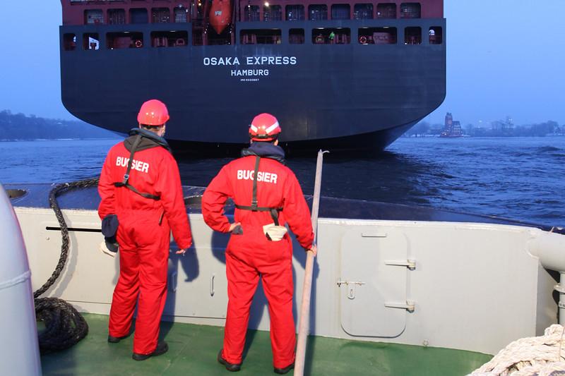 Schlepper und Containerschiff mit Menschen auf der Elbe in Hamburg Osaka Express