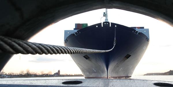 Bug Containerschiff mit Schleppleine am Schleppbock auf der Elbe Hamburg