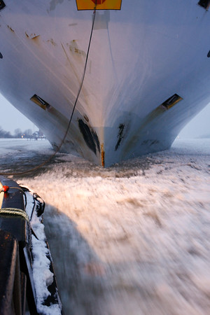 Bug Containerschiff im Winter mit Eis Schlepper auf der Elbe bei Hamburg