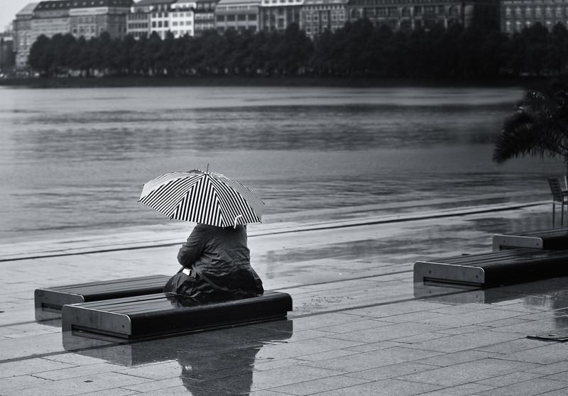 Eine Frau sitzt im Regen mit Regenschirm auf dem Jungfernstieg in Hamburg