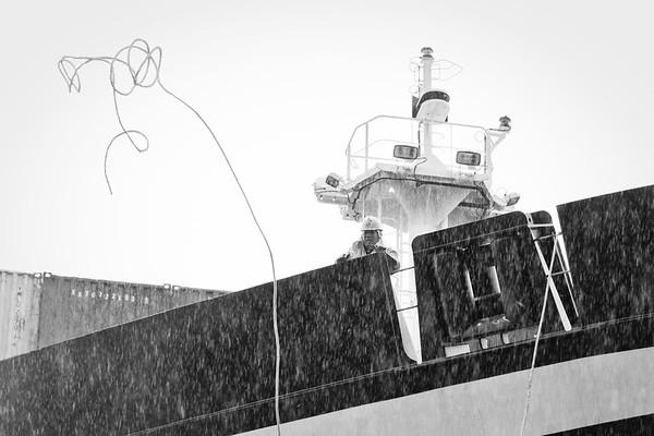 Containerschiff Decksmann auf dem Bug wirft die Wurfleine zum Schlepper schwarz-weiß
