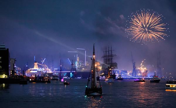 Feuerwerk und blaues Licht und Kreuzfahrtschiff auf der Elbe in Hamburg