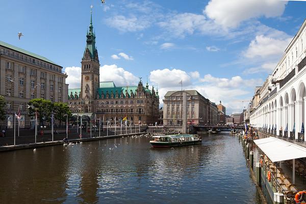 Alster Rathaus Hamburg mit Barkasse und Alsterarkaden blauer Himmel