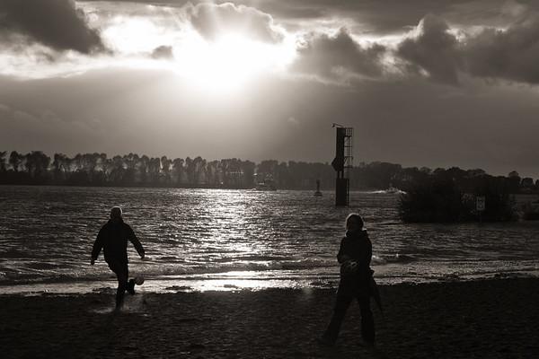 Menschen am Elbstrand schwarz-weiß im Gegenlicht Hamburg