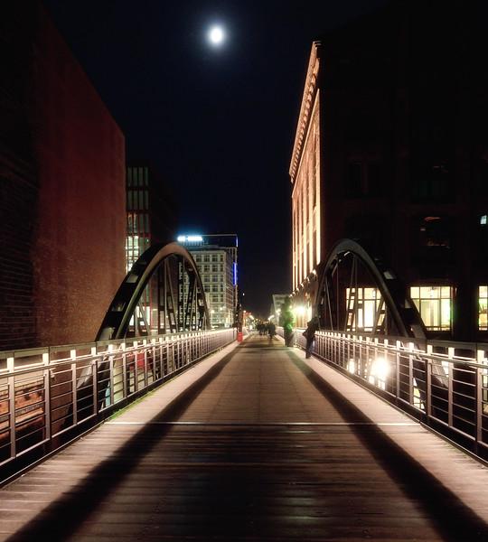 Kibbelsteg Speicherstadt Hamburg bei Nacht mit Mond und Menschen
