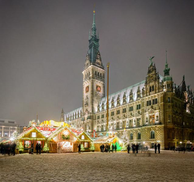 Hamburger Rathaus mit Weihnachtsmarkt und Schnee mit Menschen in der Nacht