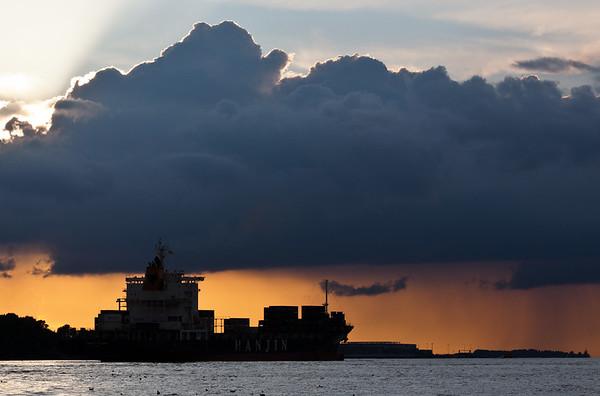 Containerschiff mit Schauerwolken am Tag auf der Elbe Hamburg