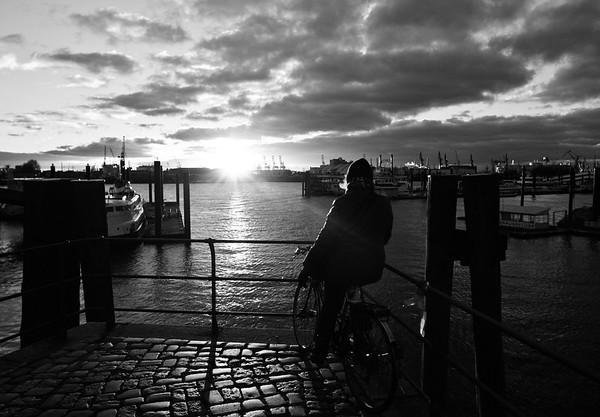 Hamburg City Sportboothafen Aussicht auf das Wasser mit Menschen auf Fahrrad in Schwarzweiß Sonne Gegenlicht