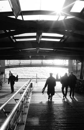 Landungsbrücken Brücke 3 Hamburg mit Menschen im Gegenlicht am Tag schwarz-weiß