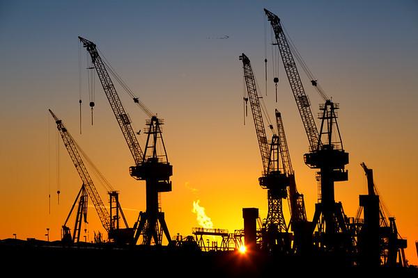 Werftkräne beim Sonnenuntergang mit Vögeln In Formation Hamburg Blohm und Voss