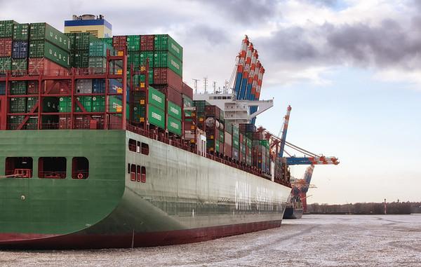 Containerschiff am EuroKai Waltershofer Hafen in Hamburg mit Eis auf der Elbe