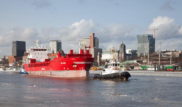 Containerschiff vor den Landungsbrücken mit 2 Schleppern Hamburg mit Eis auf der Elbe am Tag