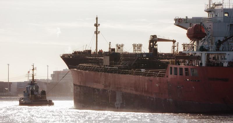 Schlepper Wilhelmine und Tankschiff im Köhlbrand mit Eis auf der Elbe im Gegenlicht