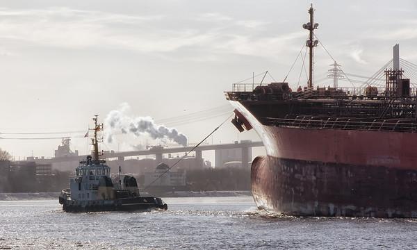 Eis auf der Elbe mit Containerschiffen und Tankschiff und Schlepper Wilhelmine im Winter Hamburg im Gegenlicht