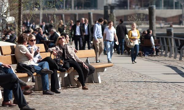 Hamburg HafenCity mit Menschen die sich in der Sonne auf der Bank entspannen am KaiserKai