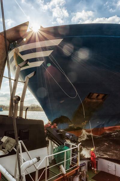 Containerschiff und Schlepper bei Sonnenschein beim anbinden