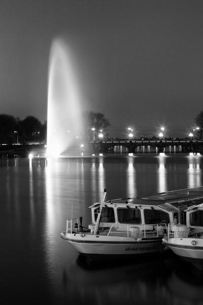 Wasserfontäne Binnenalster Hamburg mit Alsterdampfer schwarz-weiß am Abend