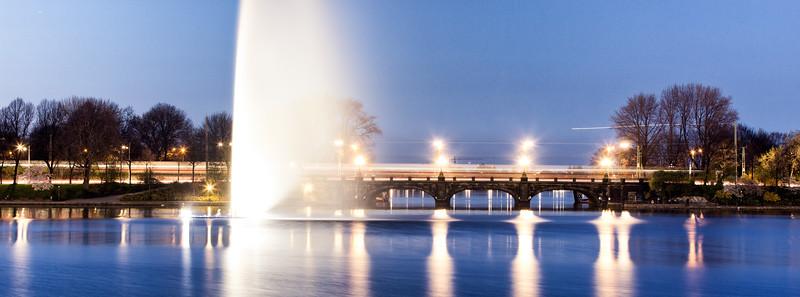 Lombardsbrücke mit Wasserfontäne und ICE Hamburg am Abend