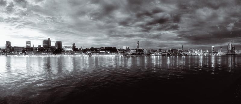 Skyline von Hamburg bei Dämmerung in schwarz-weiß gegenüber Landungsbrücken