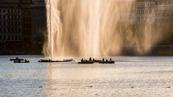 Binnenalster mit Booten Wasserfontäne Hamburg im Gegenlicht bei Sonne