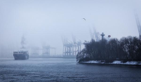 Containerschiff im vor Hafen Hamburg im Winter bei nebligem Wetter