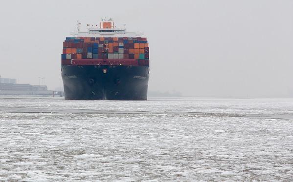 Containerschiff auf der Elbe mit Eisgang bei Hamburg