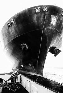 Schlepper bindet an Containerschiff an