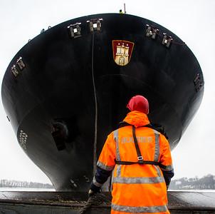 Schiffsmechaniker von BUGSIER bindet Containerschiff