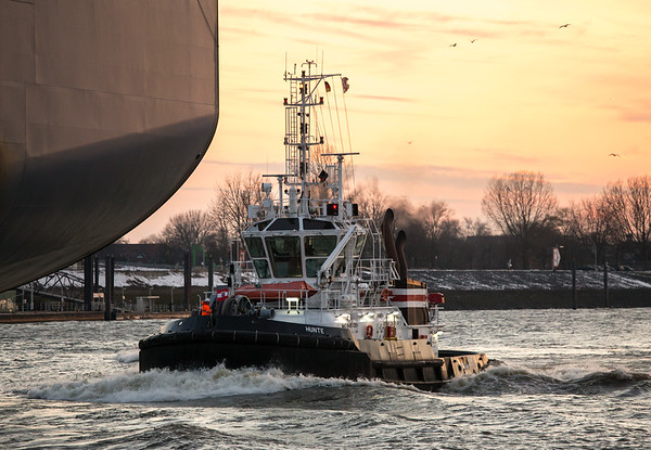 Schlepper in voller Fahrt hinter Containerschiff