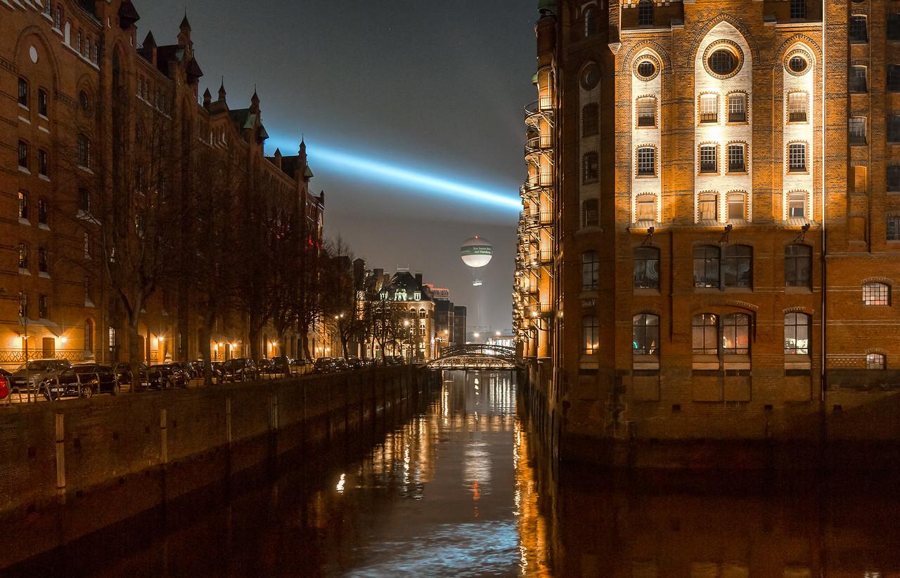 Speicherstadt am Abend mit Scheinwerfer Kunstwerk und Fesselballon