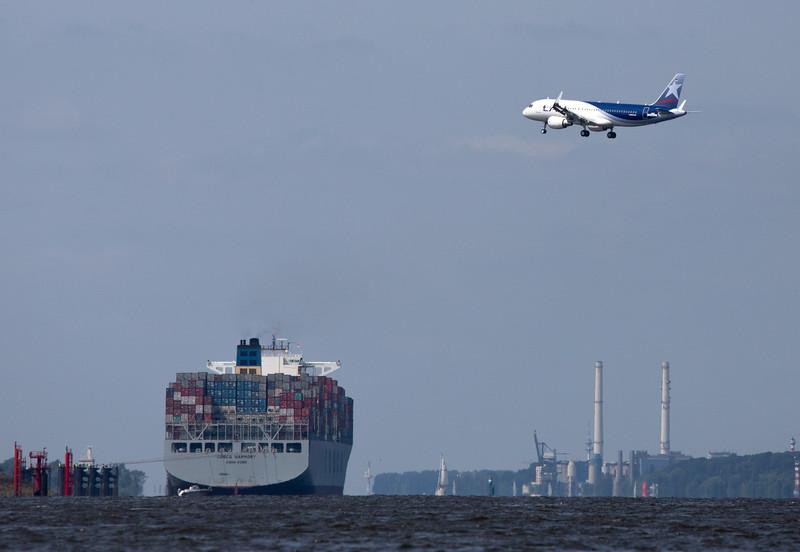 Airbus landet auf dem Betriebsflughafen in Finkenwerder vor einem großen Containerschiff auf der Elbe in Hamburg