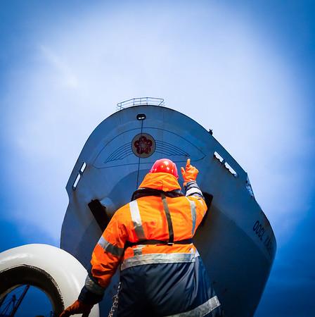 Schlepper bugsier 5 vor Containerschiff auf der Elbe mit Decksmann Hamburg