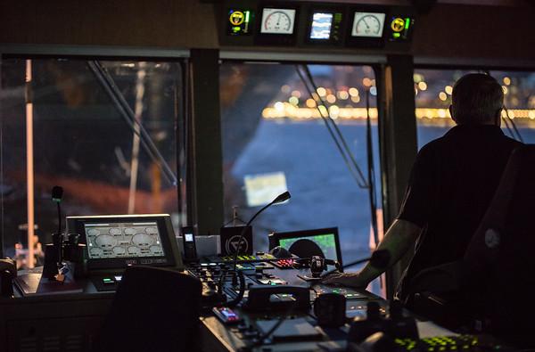 Schlepper auf der Brücke mit Kapitän am Ruder bei Nacht