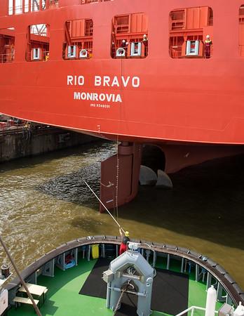 Hafenschlepper bindet an Containerschiff am